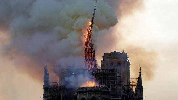The steeple of the landmark Notre-Dame Cathedral collapses as the cathedral is engulfed in flames in central Paris on April 15, 2019. - A huge fire swept through the roof of the famed Notre-Dame Cathedral in central Paris on April 15, 2019, sending flames and huge clouds of grey smoke billowing into the sky. The flames and smoke plumed from the spire and roof of the gothic cathedral, visited by millions of people a year. A spokesman for the cathedral told AFP that the wooden structure supporting the roof was being gutted by the blaze. (Photo by Geoffroy VAN DER HASSELT / AFP)        (Photo credit should read GEOFFROY VAN DER HASSELT/AFP/Getty Images)