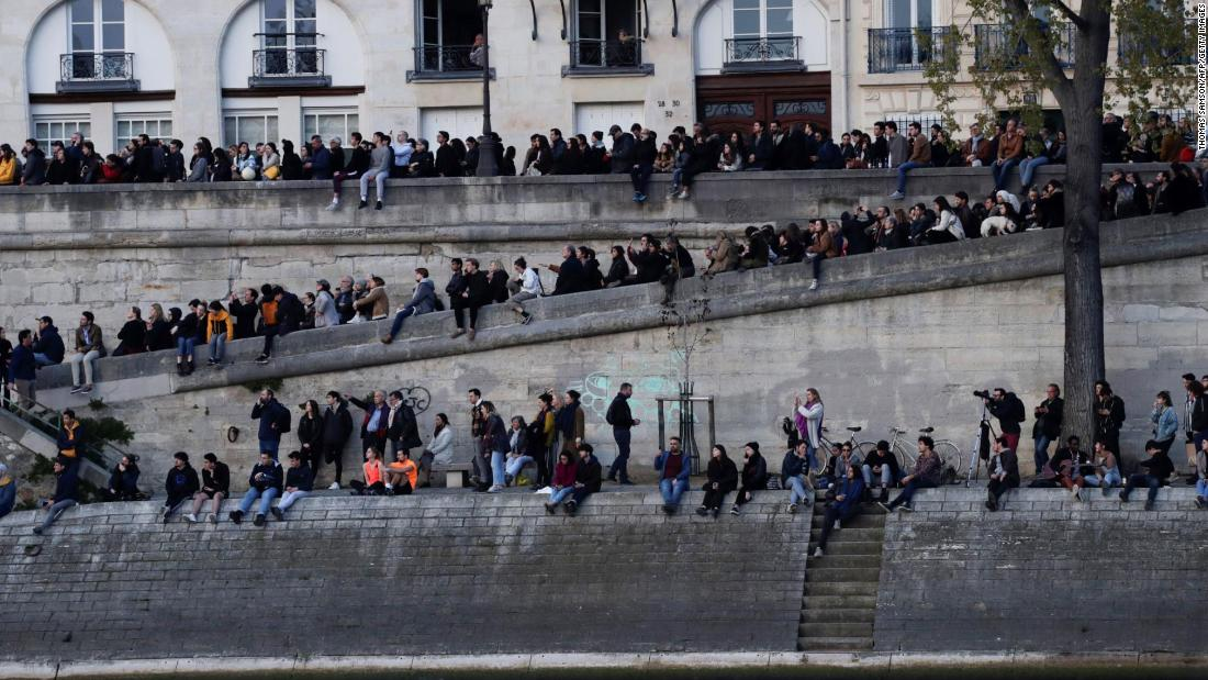 People gather on the banks of the Seine to watch the fire's progress.