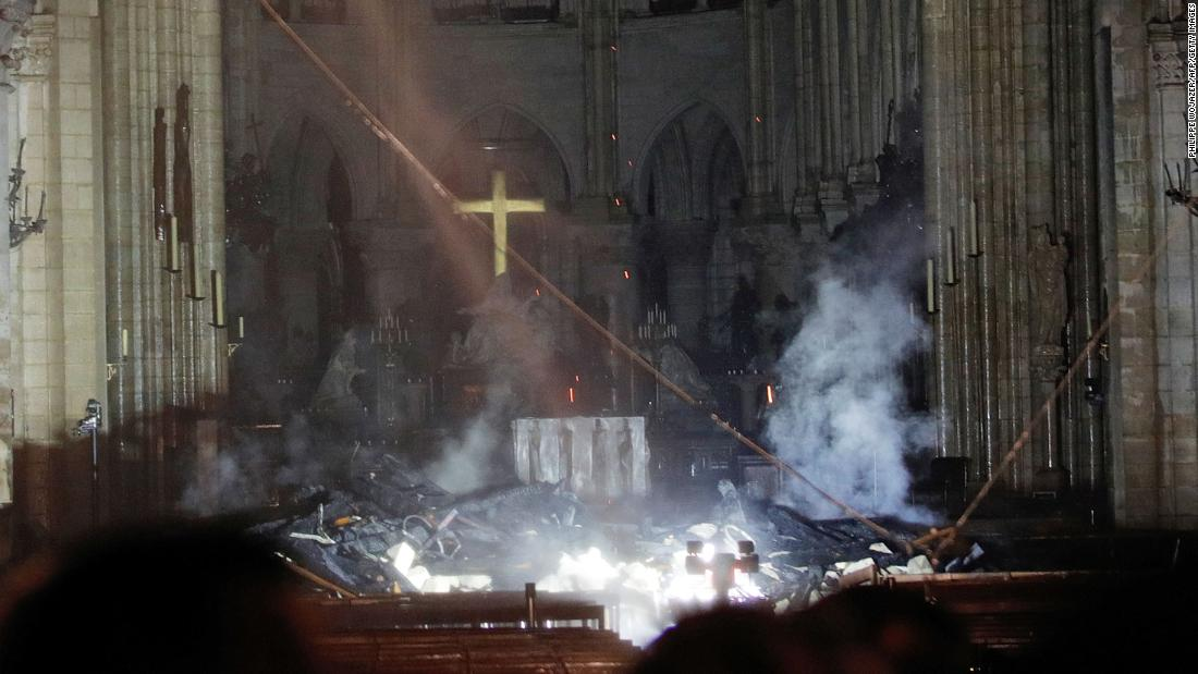 Smoke rises in front of the altar cross inside Notre Dame Cathedral.