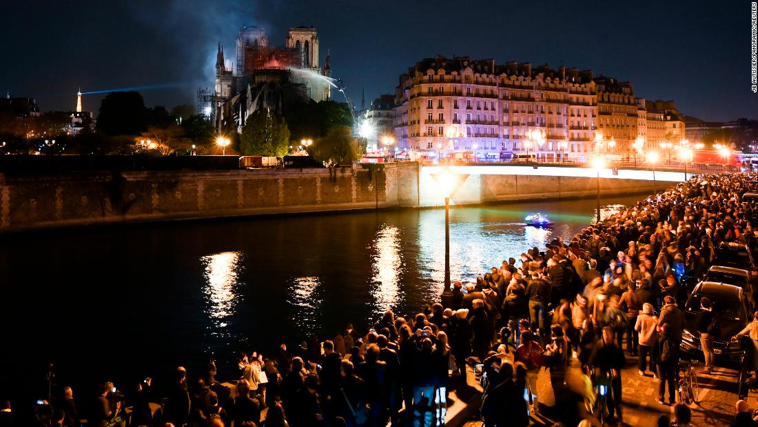 Crowds gathered on the banks of the Seine watch the firefighters' progress.