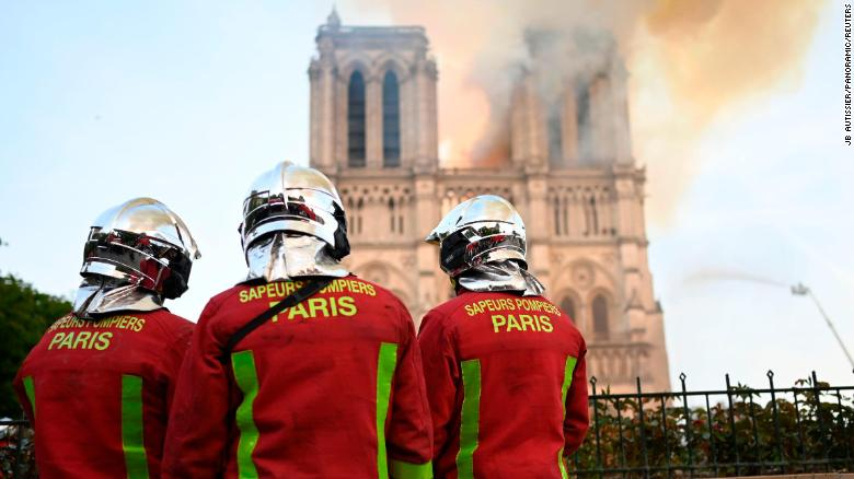 Firefighters stand near Notre Dame.