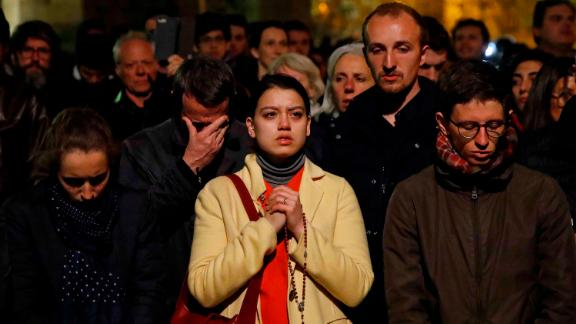 People pray as Notre Dame Cathedral burns on Monday evening.