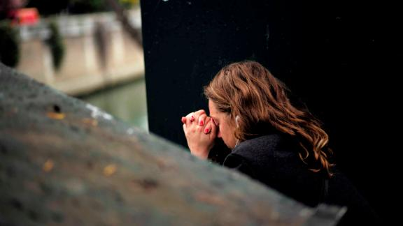 A woman reacts near Notre Dame the morning after the devastating fire.