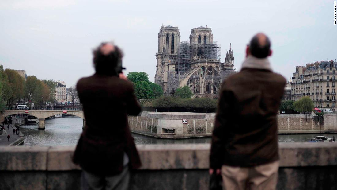 People stop to view Notre Dame Cathedral on Tuesday morning.