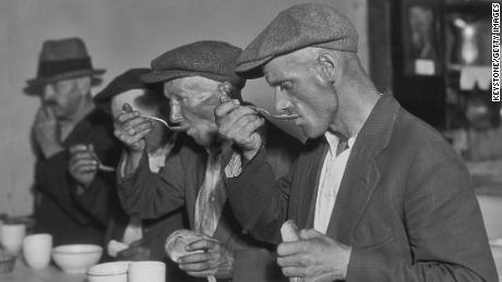 Unemployed men eat soup and bread at a cafeteria circa 1935.
