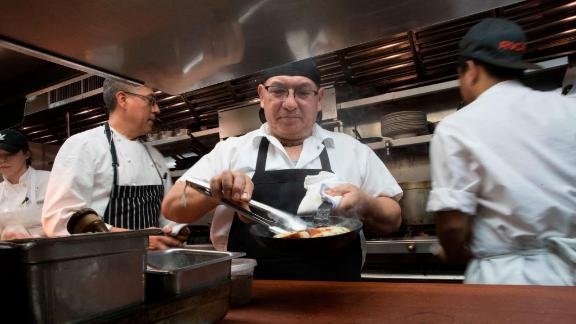 Chef Jacinto Guadarrama prepares dishes at Gotham Bar and Grill in New York, where hourly wages have gone up along with the city's minimum wage, to $15 as of the end of December.
