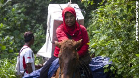 An Indonesian election worker on horseback transports ballot boxes and election material to a remote village in Jember, East Java on April 15, 2019.
