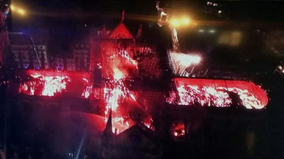 A handout image photographed on a television screen shows an aerial view of Notre Dame Cathedral engulfed in flames on Monday, April 15, 2019.