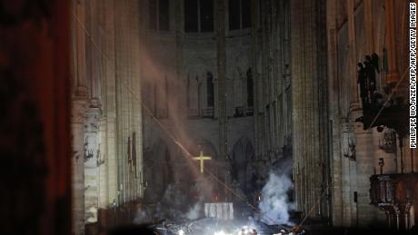 Smoke rises in front of the altar cross at Notre-Dame Cathedral in Paris on April 15, 2019, after a fire engulfed the building.