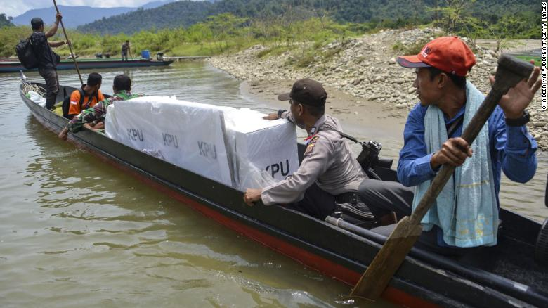 Indonesian election officials transport ballot boxes to a remote village by boat along a river in Manggamat, Southern Aceh province on April 16, 2019.