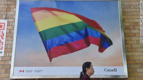In this photo taken on May 18, 2018 a woman walks past a poster of a rainbow flag outside the Canadian embassy in Beijing. - China's LGBT community may not get much support from authorities, but in a sign of growing tolerance in Chinese society, people are using the power of hashtag campaigns to denounce attacks on gays and lesbians. (Photo by GREG BAKER / AFP)        (Photo credit should read GREG BAKER/AFP/Getty Images)