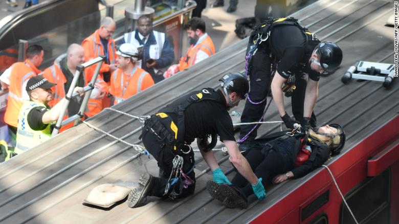 Police remove a climate change protestor from the roof of a London train.
