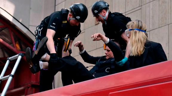 Police begin to remove climate activists who glued themselves to a train in London on April 17.