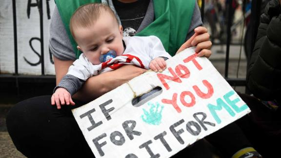 A infant is held alongside a protest sign in Parliament Square, London, on Tuesday.