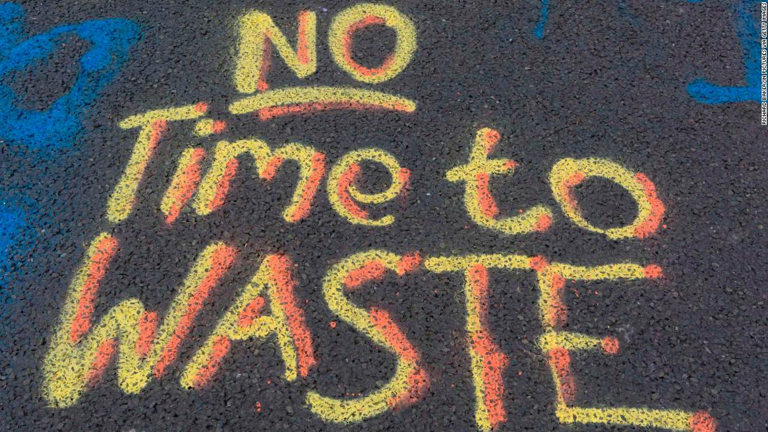 """No Time to Waste"" is written on the pavement at Waterloo Bridge."