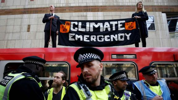 Climate activists hold a sign on top of a Dockland Light Railway train at Canary Wharf station, in east London, as part of ongoing climate change protests in the English capital.
