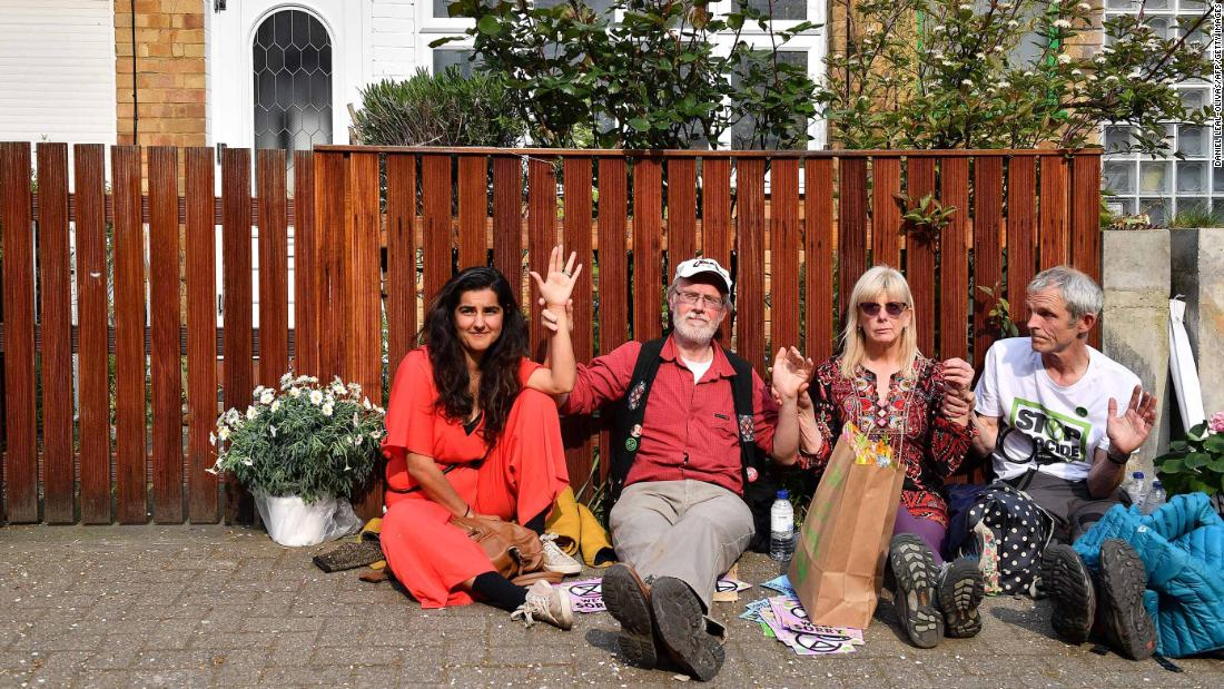 Activists, including Labour Party councilor Skeena Rathor, left, are photographed with their hands glued together and locked to a fence outside the home of Labour Party leader Jeremy Corbyn in north London on April 17.