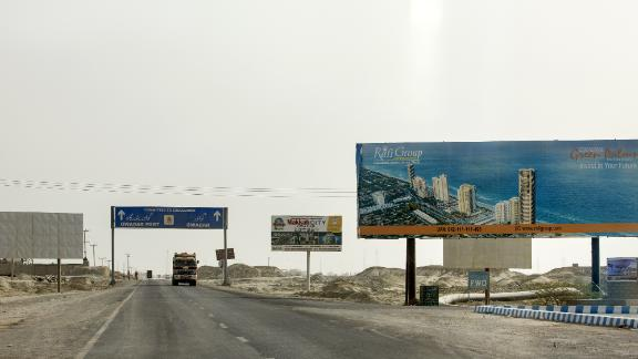 A billboard advertisement for a housing development stands along a highway on the outskirts of Gwadar, Balochistan, Pakistan, on Monday, July 3, 2018. What used to be a small fishing town on the southwestern corner of Pakistan is giving way for construction of roads and buildings to house banks, insurance and clearing agents. China Overseas Port Holdings, Gwadar Ports operator, has separately spent $250 million to add five new cranes, construct a building in less than six months by importing ready made parts and create space for a free zone. Photographer: Asim Hafeez/Bloomberg via Getty Images