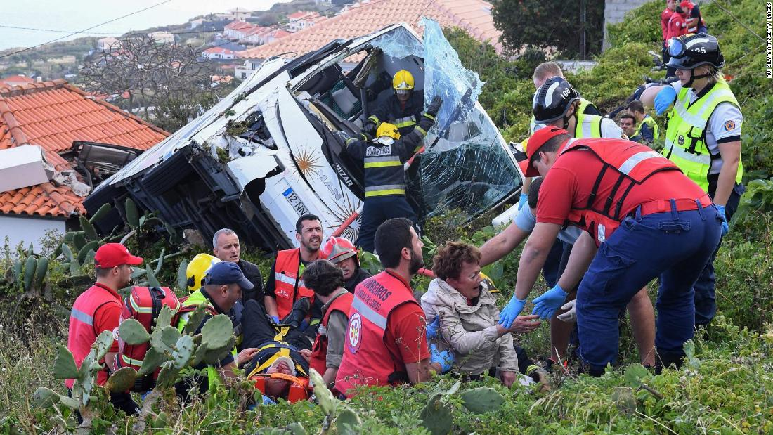 Firefighters help victims at the site of a tourist bus crash on Wednesday, April 17, on the Portuguese island of Madeira. At least 28 people were killed and another 28 were injured as a result of the crash.