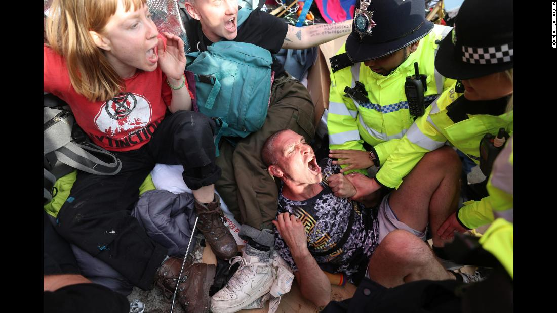 Police officers detain climate change activists during an Extinction Rebellion protest in London on Thursday, April 18.