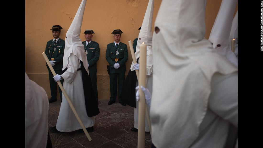 "Members of the Spanish Civil Guard watch as penitents of the ""Estrella"" brotherhood walk during a Holy Week procession on Wednesday, April 17."