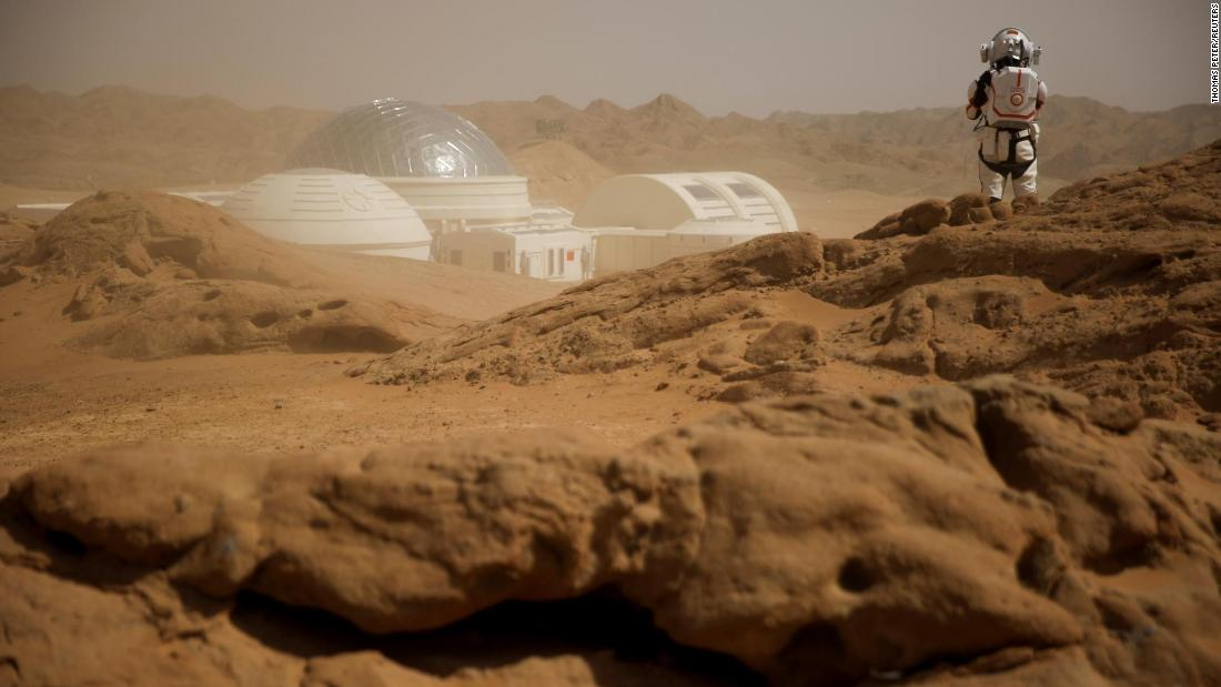 A staff member wearing a mock space suit looks out at the C-Space Project Mars simulation base in the Gobi Desert outside Jinchang, Gansu Province, China, on Thursday, April 18.