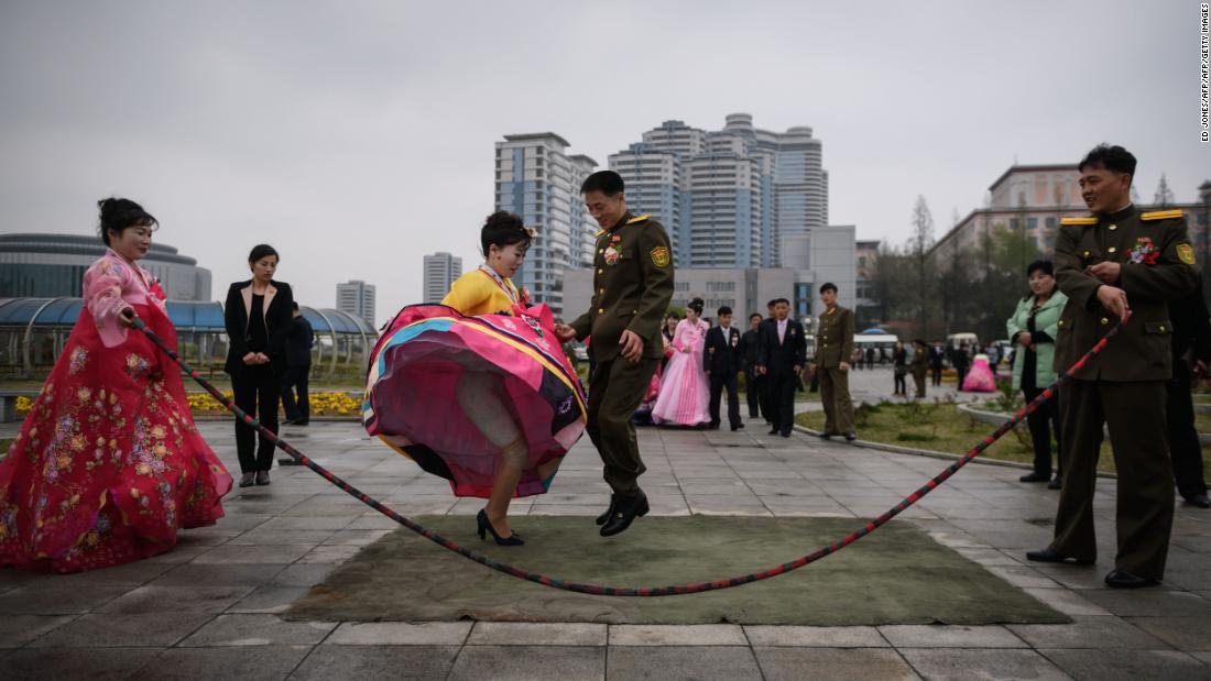 A bride and groom jump over a skipping rope as they partake in a wedding photo shoot in Pyongyang on Thursday, April 18.