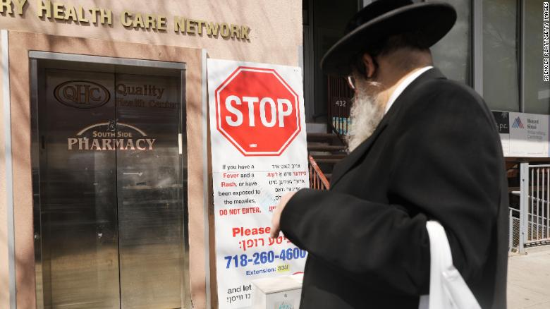 Signs warn of the dangers of a persistent measles outbreak in Williamsburg.