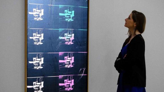 "A member of the auction house staff poses with ""Fourteen Small Electric Chairs"" by Andy Warhol (est. £4,000,000-6,000,000) during a photocall on February 1, 2016 to promote Bonham's upcoming ""Post-War and Contemporary Art"" sale in London.  The sale takes place on February 11 with items by artists including Kazuo Shiraga, Frank Auerbach and Germaine Richier.  / AFP / LEON NEAL / RESTRICTED TO EDITORIAL USE - MANDATORY MENTION OF THE ARTIST UPON PUBLICATION - TO ILLUSTRATE THE EVENT AS SPECIFIED IN THE CAPTION        (Photo credit should read LEON NEAL/AFP/Getty Images)"