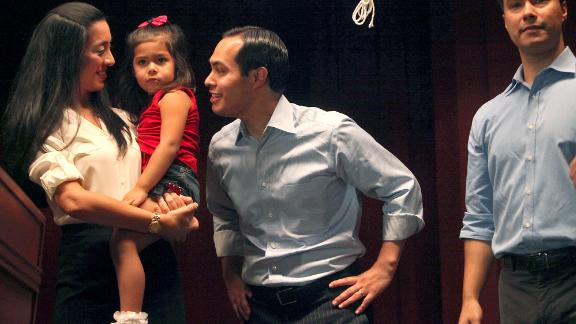 Castro, center, is joined on stage with his wife, Erica, and their daughter, Carina, at an event in September 2012. Castro's brother, Joaquin, is at right.