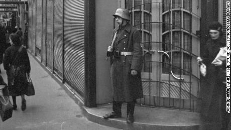 A guard stands outside Schiffmann's department store, a Jewish business, after it was taken over by the Nazis.