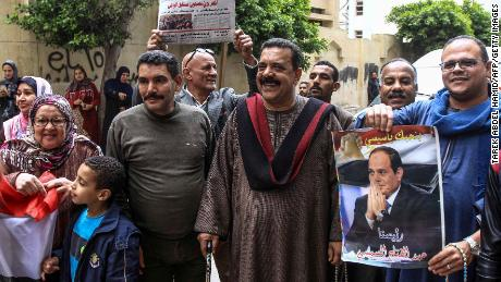Egyptians pose with a newspaper and a poster of President Abdel Fattah al-Sisi outside an Alexandria school as voting gets underway Saturday on constitutional amendments.