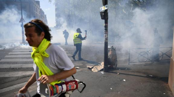 """Protesters take cover from tear gas during an anti-government demonstration called by the """"Yellow Vests"""" (gilets jaunes) movement, on April 20, 2019 in Paris. (Photo by Anne-Christine POUJOULAT / AFP)        (Photo credit should read ANNE-CHRISTINE POUJOULAT/AFP/Getty Images)"""