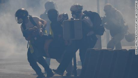 "So- called "" street medics "" carry an injured protester amid tear gas."