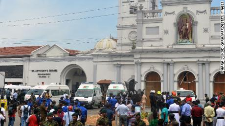 Ambulances are seen outside the church premises with gathered people and security personnel following a blast at the St. Anthony's Shrine in Kochchikade, Colombo on April 21, 2019. - Explosions have hit three churches and three hotels in and around the Sri Lankan capital of Colombo, police said on April 21. (Photo by ISHARA S.  KODIKARA / AFP)        (Photo credit should read ISHARA S.  KODIKARA/AFP/Getty Images)