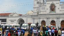 Ambulances are seen outside the church premises with gathered people and security personnel following a blast at the St. Anthony's Shrine in Kochchikade, Colombo on April 21, 2019. - Explosions have hit three churches and three hotels in and around the Sri Lankan capital of Colombo, police said on April 21. [Photo by ISHARA S. KODIKARA / AFP) (Photo credit should read ISHARA S. KODIKARA/AFP/Getty Images)