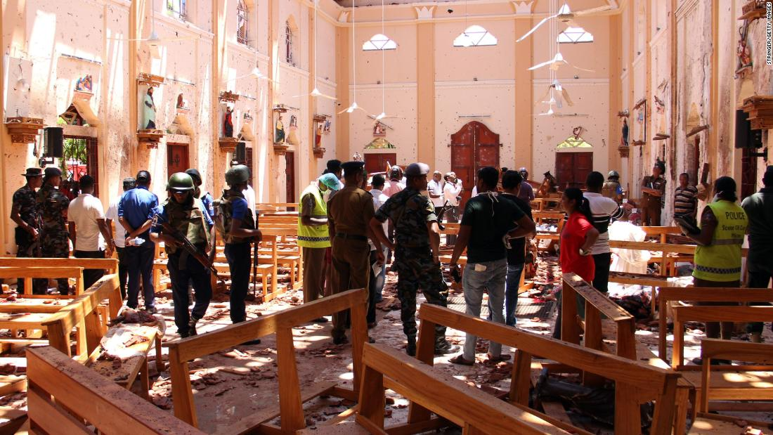 Sri Lankan security personnel walk through debris following an explosion at Negombo's St. Sebastian's Church.