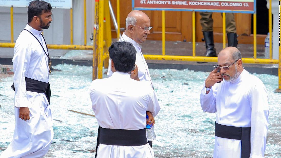 Priests view blast debris outside St. Anthony's Shrine.