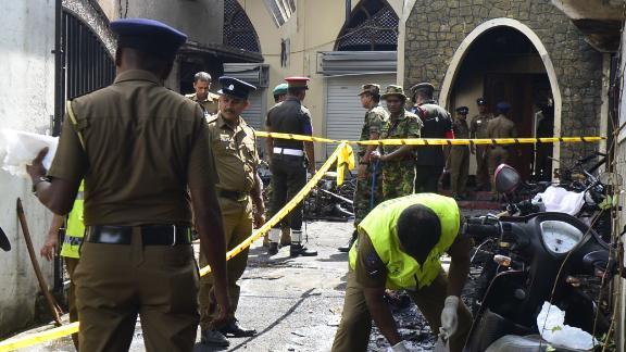 Security personnel and investigators sift through debris outside Zion Church in Batticaloa.