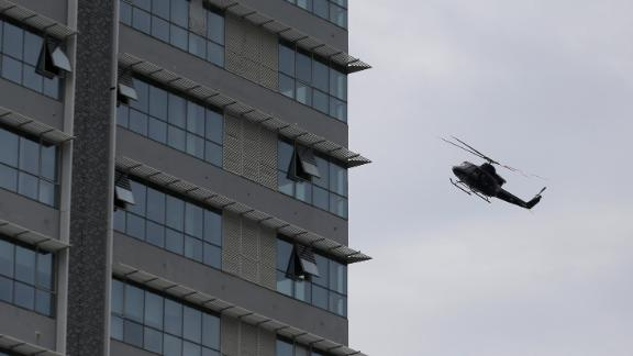 A Sri Lankan Air Force helicopter flies over a  house suspected to be a hideout of militants following a shootout in Colombo.
