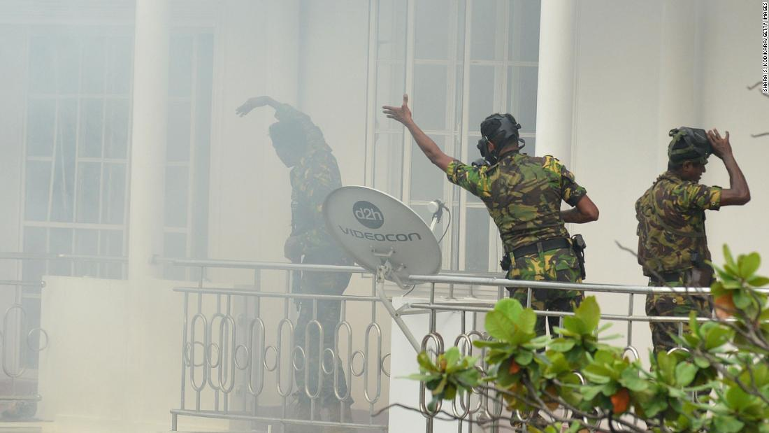Sri Lankan Special Task Force  personnel gesture outside a house during a raid following an explosion at a property in the Orugodawatta district of Colombo.