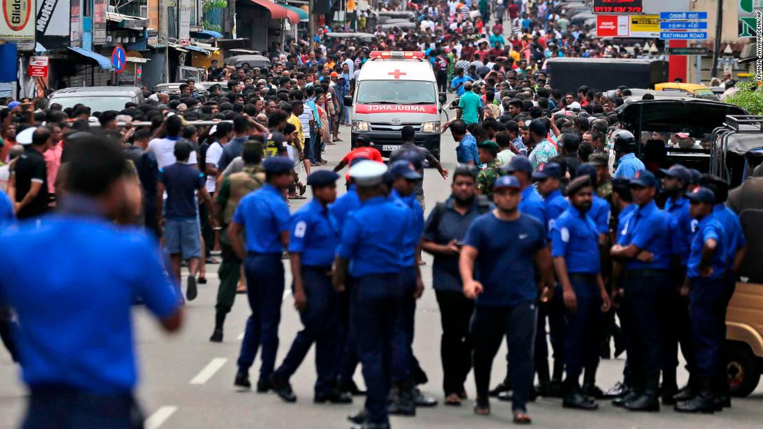 Sri Lankan police officers clear the road as an ambulance drives through carrying injured from bomb blasts in Colombo.