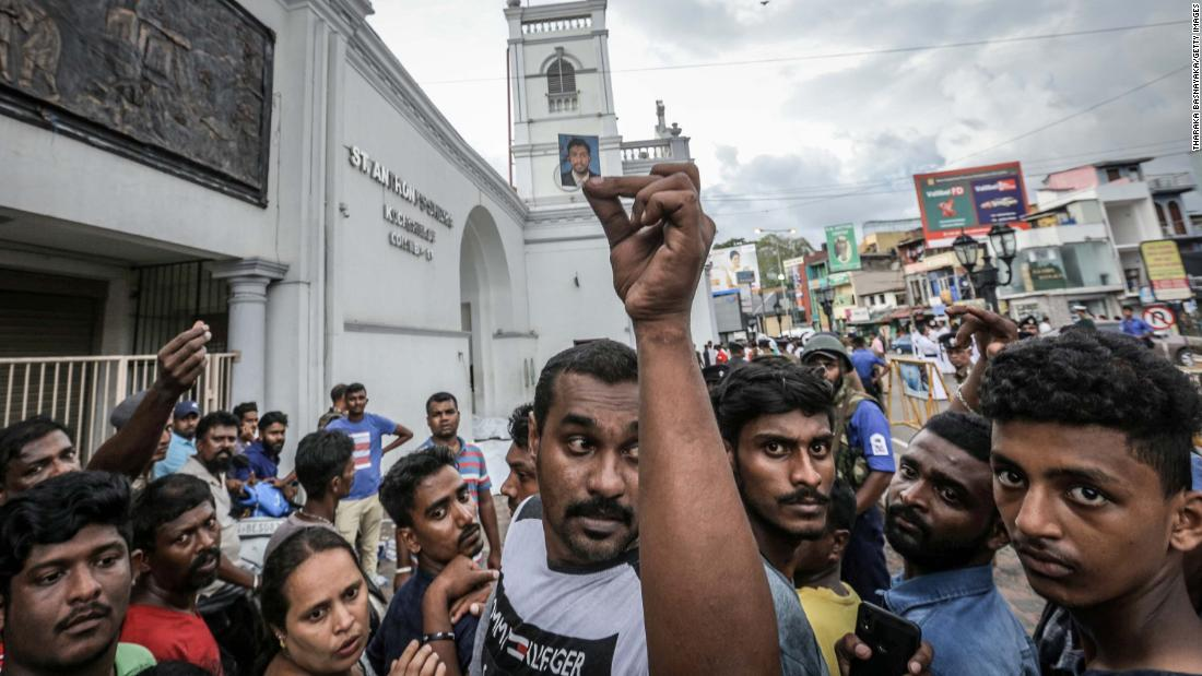 A man holds up a blood-stained photograph  as people wait to identify the  bodies of their loved ones in front of St. Anthony's Church.