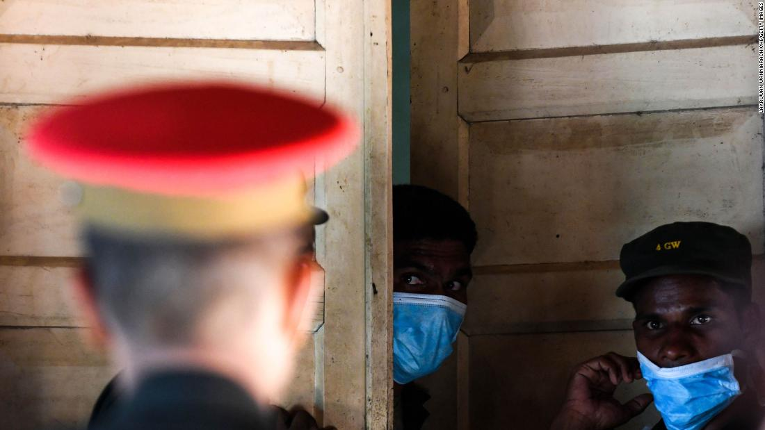Sri Lankan hospital workers and soldiers stand at the door to a morgue following a blast in a church in Batticaloa.