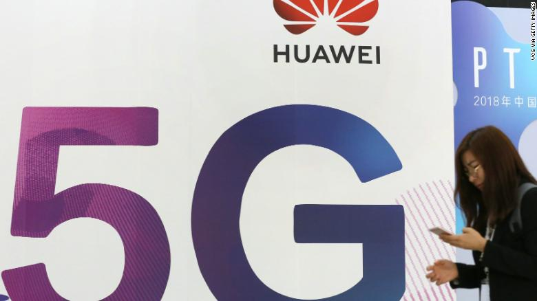 A woman walks past the stand of Huawei featuring 5G technology during the PT Expo China at Beijing National Convention Center.