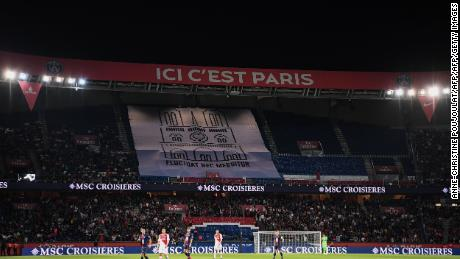 "PSG fans hold aloft a banner showing a drawing of Notre-Dame with the Paris city motto: ""Fluctuat Nec Mergitur"" (""She is tossed but not sunk"")"