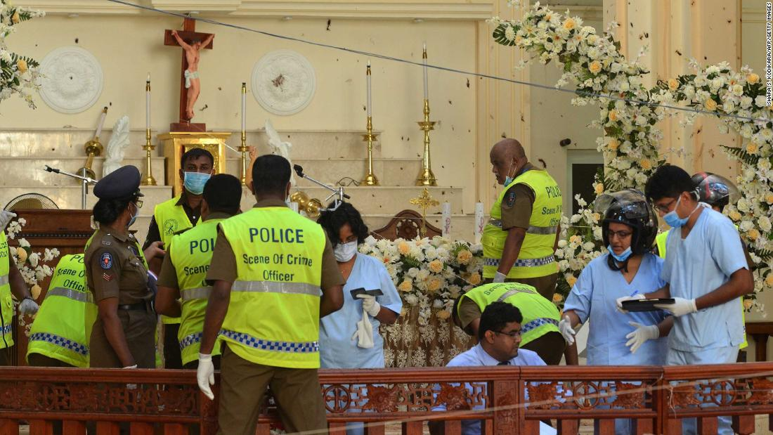 Police and forensics officials inspect the interior of St. Sebastian's Church in Negombo on Monday, April 22.