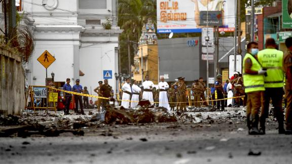 Sri Lankan priests look at the debris of a car after it explodes when police tried to defuse a bomb near St. Anthony