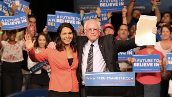 Gabbard and Democratic presidential candidate Bernie Sanders wave to supporters during a campaign event in Miami in March 2016. Gabbard left the Democratic National Committee to endorse Sanders' presidential bid.