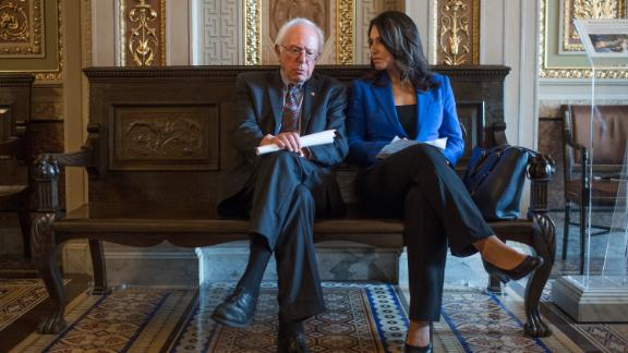 In May 2017, Gabbard and Sanders sit in the Capitol's Senate Reception Room before a news conference introducing legislation that would incrementally raise the nation's minimum wage to $15 an hour.